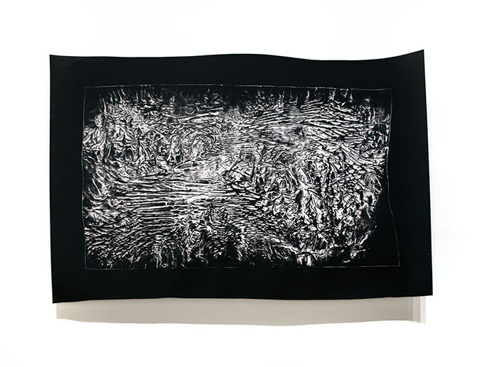 Abstract, black and white photogram made from an altered and ink smeared plastic surface